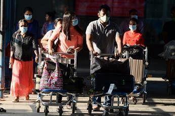 சென்னை அனைத்துலக விமான நிலையத்தில் முகக்கவசங்களுடன் பயணிகள். படம்: ஏஎஃப்பி